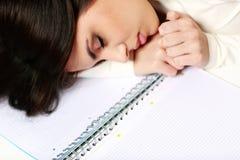 Dormido caido estudiante cansado en la tabla Imagenes de archivo