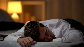 Dormido caido hombre de negocios con exceso de trabajo en la cama, cansada después de día laborable duro imagen de archivo libre de regalías