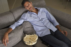Dormido caido hombre hispánico en Sofa Watching TV Imagen de archivo