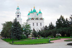 Dormition Cathedral in Astrakhan Kremlin surrounded by green trees. Stock Photos
