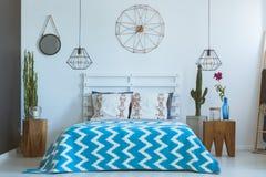 Dormitorio étnico, reloj de cobre, lámparas Imagen de archivo libre de regalías