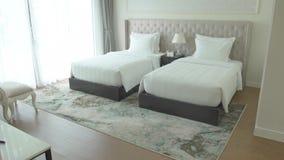 Dormitorio acogedor con las camas cómodas y muebles en interior moderno de la casa Dormitorio con la ventana panorámica y acogedo almacen de video