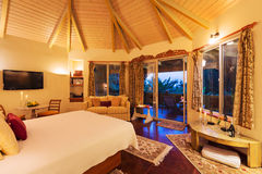 Dormitorio acogedor con los suelos de parqué en la puesta del sol Foto de archivo