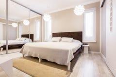 Dormitorio beige con el guardarropa del espejo imágenes de archivo libres de regalías