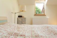 Dormitorio brillante con la pequeña ventana foto de archivo