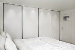 Dormitorio. Cama y un armario. Fotos de archivo libres de regalías