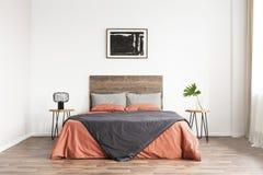 Dormitorio clásico mínimo con la cama de madera, las hojas de lino coralinas y las ilustraciones blancos y negros fotografía de archivo libre de regalías
