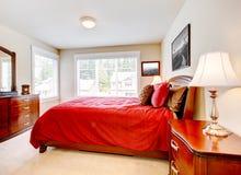 Dormitorio con dos ventanas y la cama roja fotos de archivo