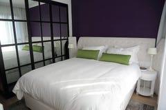Dormitorio con el espejo duble grande de la cama y de la pared Foto de archivo libre de regalías
