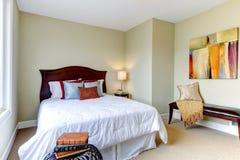 Dormitorio con el lecho blanco, paredes verdes. Foto de archivo
