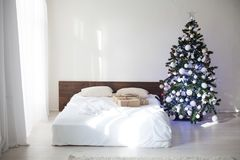 Dormitorio con la cama de la decoración del árbol del Año Nuevo de la Navidad Fotografía de archivo libre de regalías