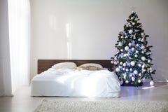 Dormitorio con la cama de la decoración del árbol del Año Nuevo de la Navidad Imagen de archivo