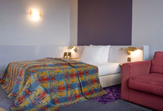 Dormitorio con la cama gigante y el sofá del aplique Imágenes de archivo libres de regalías