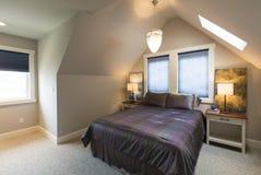 Dormitorio con la cama, las mesitas de noche, el techo saltado, las cubiertas de ventana y la iluminación del acento en interior  Imagenes de archivo