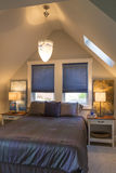 Dormitorio con la cama, las mesitas de noche, el techo saltado, las cubiertas de ventana y la iluminación del acento en interior  Fotos de archivo