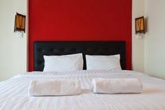 Dormitorio con la pared roja, toalla en la cama. Foto de archivo