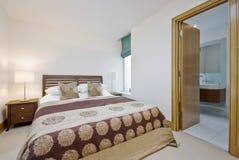 Dormitorio con la puerta abierta al cuarto de baño de la en-habitación fotos de archivo