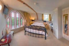 Dormitorio con la ventana de cristal de colores (el campanario de una iglesia) Fotografía de archivo