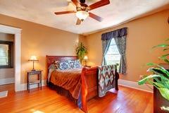 Dormitorio con las paredes de Brown y la madera dura de la cereza Imagen de archivo