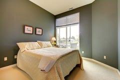 Dormitorio con las paredes verdes grises y el lecho blanco. Imagenes de archivo