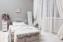 Dormitorio con una cama blanca, espejo grande de la tarde cerca de la ventana en Imagen de archivo