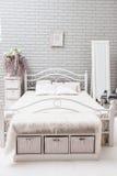 Dormitorio con una cama blanca, espejo grande de la tarde cerca de la ventana en Fotografía de archivo