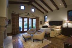 Dormitorio con zona para sentarse en casa Fotos de archivo