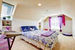 Dormitorio de la muchacha con el techo del ático y alfombra beige con los juguetes. Foto de archivo
