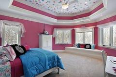 Dormitorio de la muchacha con las paredes rosadas imagen de archivo