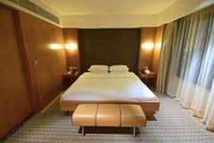 Dormitorio de lujo con el bedsheet, el banco y la cortina blancos limpios Fotos de archivo