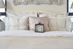 Dormitorio de lujo con el despertador clásico del estilo en cama foto de archivo