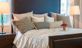 Dormitorio de lujo con las almohadas marrones del modelo y la bandeja decorativa en cama foto de archivo