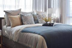 Dormitorio de lujo con las almohadas rayadas y juego de té decorativo en cama fotos de archivo libres de regalías