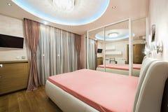 Dormitorio de lujo con las luces de techo modernas Imagen de archivo libre de regalías