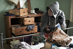 Dormitorio de Stealing Items From del ladrón durante rotura de la casa adentro Imagenes de archivo
