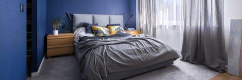 Dormitorio del azul de cobalto con la cama fotografía de archivo