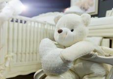Dormitorio del bebé con el oso de peluche blanco imagenes de archivo