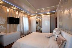 Dormitorio del diseño moderno en colores de oro Foto de archivo