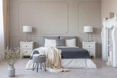 Dormitorio del estilo de Nueva York interior con el diseño simétrico, espacio de la copia en la pared gris vacía foto de archivo libre de regalías