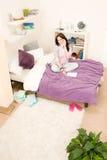 Dormitorio del estudiante - chica joven que habla en el teléfono Imagen de archivo libre de regalías