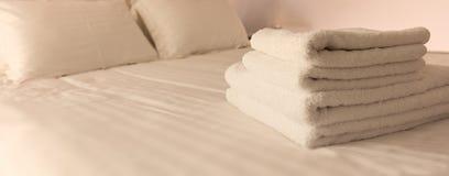 Dormitorio del hotel Hojas blancas del toalla, de lino y almohadas mullidas, dobladas en cama Ciérrese encima de la visión Fotografía de archivo