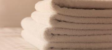Dormitorio del hotel Hojas blancas del toalla, de lino y almohadas mullidas, dobladas en cama Ciérrese encima de la visión Imagen de archivo libre de regalías