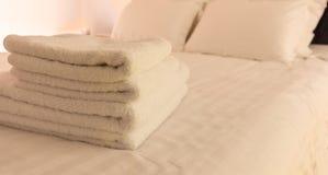 Dormitorio del hotel Hojas blancas del toalla, de lino y almohadas mullidas, dobladas en cama Ciérrese encima de la visión Fotografía de archivo libre de regalías