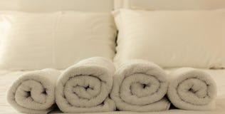 Dormitorio del hotel Toallas mullidas, rodadas blancas en fila, hojas de lino y almohadas en una cama primer Imágenes de archivo libres de regalías