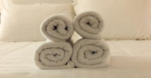 Dormitorio del ` s del hotel Hojas blancas del toalla, de lino y almohadas mullidas, rodadas en una cama Ciérrese encima de la vi Imagen de archivo