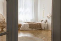 Dormitorio elegante blanco diseñado con los materiales naturales imagen de archivo