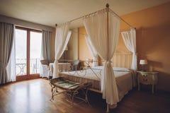 Dormitorio en colores claros Cama matrimonial cómoda grande en interior clásico elegante imagen de archivo libre de regalías