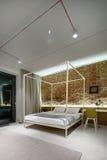Dormitorio en un estilo moderno del desván Pared de ladrillo sin yeso Cama Imágenes de archivo libres de regalías