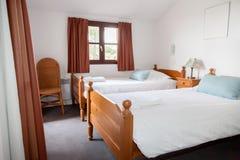 Dormitorio espacioso con lecho y paredes blancas Fotos de archivo libres de regalías