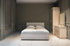 Dormitorio espacioso en gris, con muebles hechos a mano, de madera, Fotos de archivo